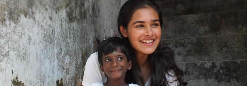 A female volunteer sites with a child in Sri Lanka