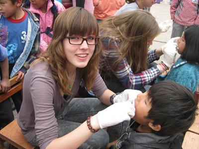 A female volunteer provides a check-up in Peru