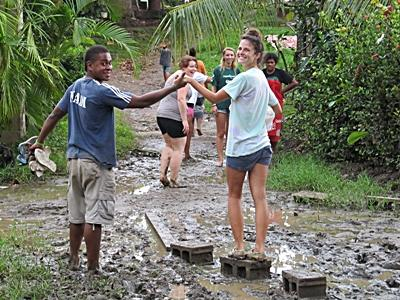 A volunteer in Fiji is assisted by local resident