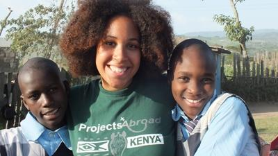 A volunteer smiling with two locals from Kenya