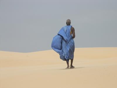 An old man walking in a desert in Senegal