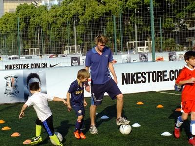 Volunteer coaching football at a sports project in China