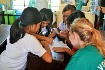 Volunteer working with children in a teaching exercise in the Philippines