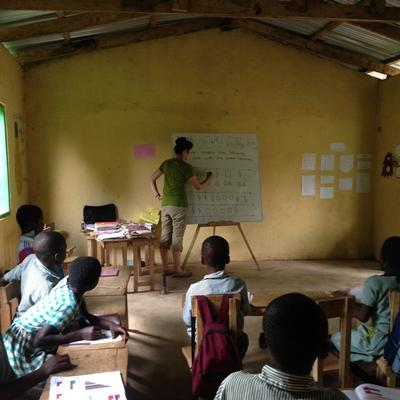 Volunteer teaches maths to a class in Ghana