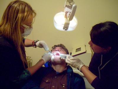 Volunteer helps local dentist with procedure